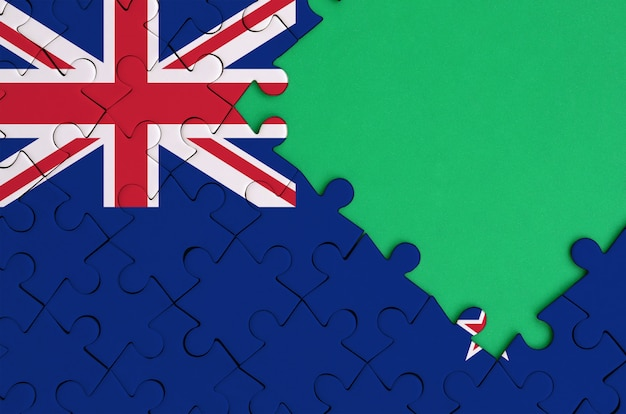 New zealand flag  is depicted on a completed jigsaw puzzle with free green copy space on the right side