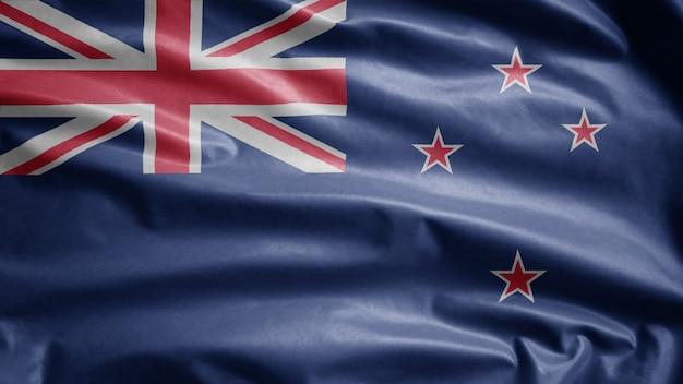 風に揺れるニュージーランドの旗。ニュージーランドのテンプレートを吹く、柔らかく滑らかなシルクのクローズアップ。布生地のテクスチャは、背景をエンサインします。