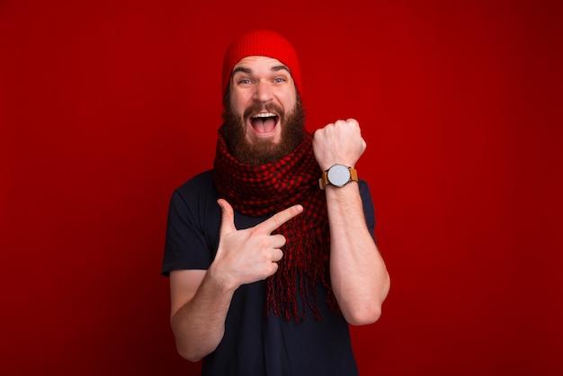 Фотография счастливого бородатого парня, указывающего на его часы newa и задержанного на встрече