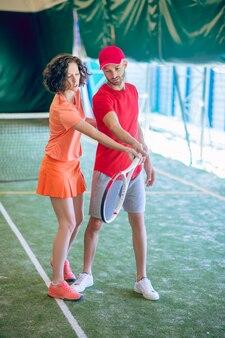 신참. 초보자에게 테니스 경기 규칙을 설명하는 여성 테니스 코치