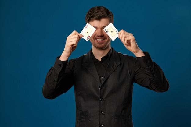 파란색 스튜디오 b에 포즈를 취하는 동안 두 개의 카드 놀이를 들고 검은 조끼와 셔츠에 포커에 초보자 ...