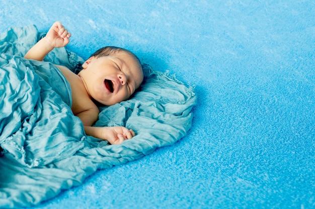 青いラップ布で泣いている彼の背中に横たわっている新生児14日古い男の子