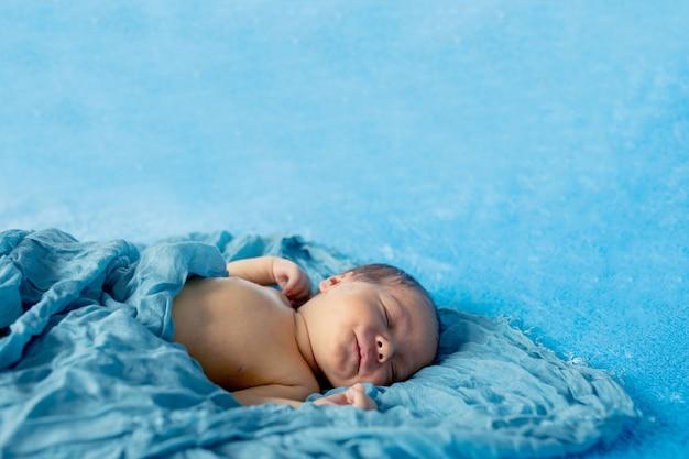 青いラップ布の下でリラックスした彼の背中に横になっている新生児14日古い男の子