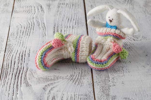 新生児発表コンセプト。アクアマリンの背景にニットのブーツ