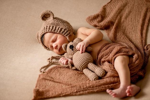 Новорожденный ребенок 10 дней спит в уютном медвежьем костюме и светло-коричневом наряде. он держит крошечного плюшевого мишку. начало жизни и концепция счастливого детства.
