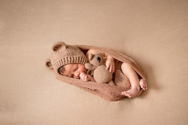 Новорожденный ребенок 10 дней спит в уютном медвежьем костюме и светло-коричневом наряде.