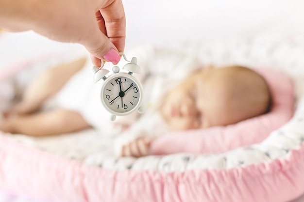 Newborn baby and alarm clock. selective focus. people.