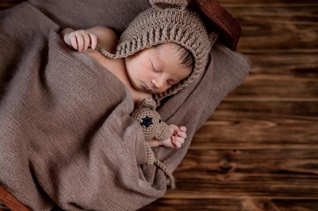 生まれたばかりの赤ちゃん、美しい幼児が横たわって、木製の背景、コピースペースのベッドで小さなテディベアを保持
