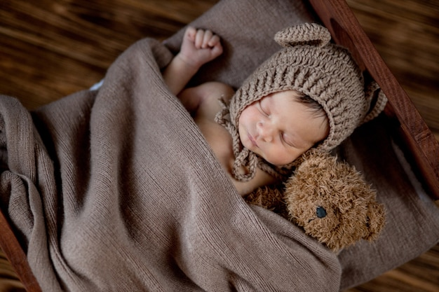 Новорожденный ребенок, красивый младенец лежит и держит крошечного плюшевого мишку в кровати на деревянной поверхности.