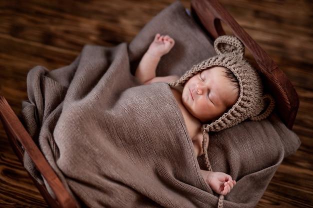 Новорожденный ребенок, красивый младенец лежит в коричневом меховом одеяле на деревянном фоне, 10-дневная девочка спит в постели. скопируйте пространство.