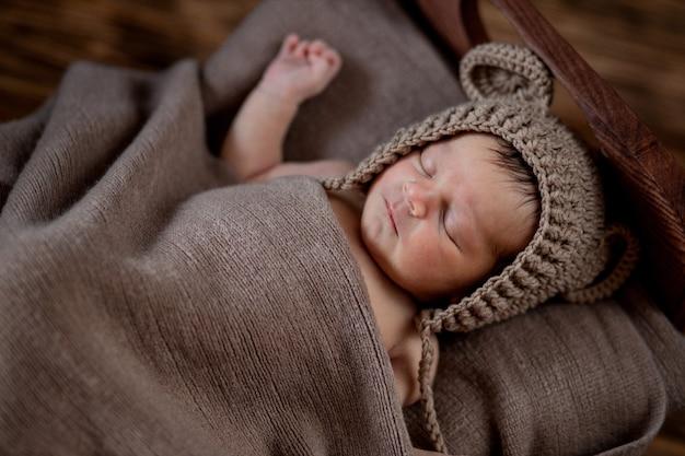 Новорожденный ребенок, красивый младенец лежит в коричневом меховом одеяле на деревянном фоне