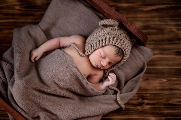 Новорожденный ребенок, красивый младенец лежит в коричневом меховом одеяле на дереве