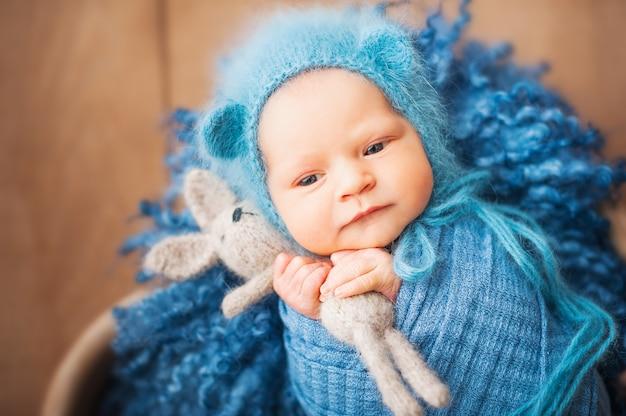 Newborn baby in blue wool in a heart-shaped basket