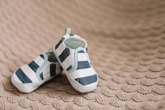 ニット生地の背景に生まれたばかりの赤ちゃんのブーツ