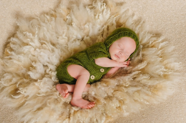 신생아, 9 일, 자고 녹색 의상 및 베이지 색 배경에 싸서.