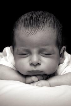 Newborn baby boy over black