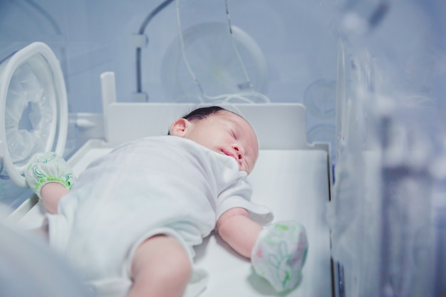 インキュベーター内の頂点で覆われた新生児の少年。