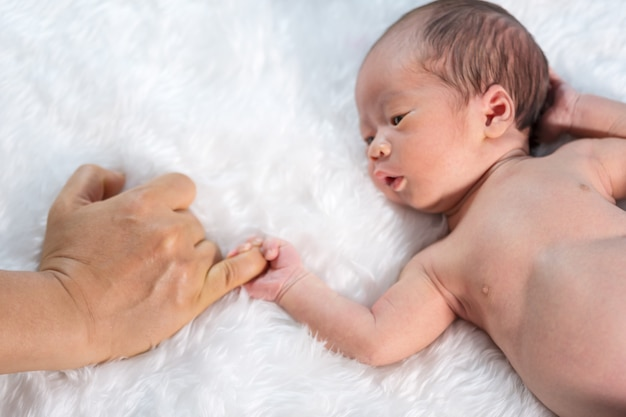 Newborn baby boy holding little finger of father's hand