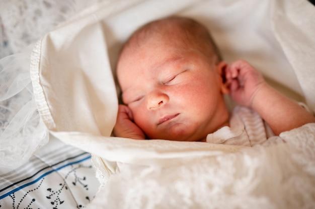 Новорожденный мальчик в постели. новорожденный ребенок в белом обвесе лежит в легкой колыбели. дети спят. постельное белье для детей. младенец спит в постели. здоровый малыш вскоре после рождения.