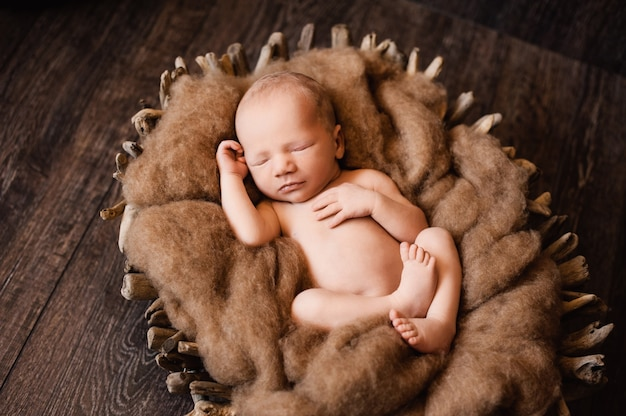 Newborn baby boy is napping in a wooden basket at a newborn photoshoot