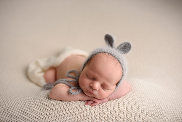 Newborn baby boy in a knitted hat sleeps on a light knitted blanket.
