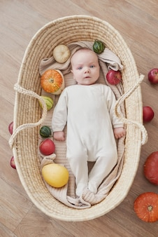 Newborn baby boy lies in wicker cradle with pumpkins and apples. happy motherhood and fatherhood. maternity hospital and clinic. father and mother day. autumn background. thanksgiving, halloween