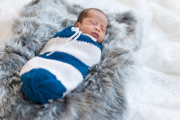 Новорожденный мальчик спит и пеленается в вязаной пленке на кровати