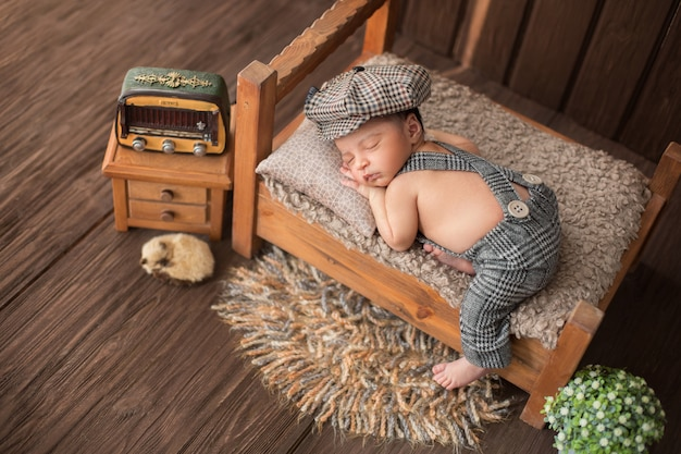 Newborn baby boy sleeping in beautiful room which includes carpet flower radio and cute animal