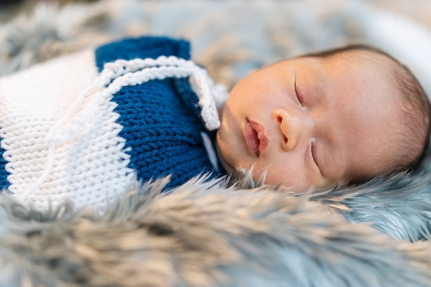 Newborn baby boy sleeping and swaddled in a knit wrap  on bed