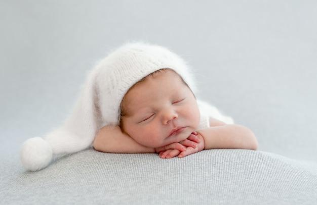 갓난 아기는 흰 모자를 쓰고 뺨 아래에 손을 잡고 자고 있습니다. 유아 아이 스튜디오 초상화