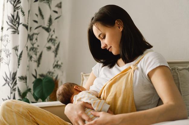 Newborn baby boy sucking milk from mother's breast