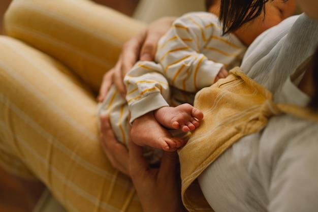Newborn baby boy sucking milk from mothers breast. portrait of mom and breastfeeding baby. concept of healthy and natural baby breastfeeding nutrition.
