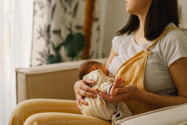 Новорожденный мальчик сосет молоко из груди матери. портрет мамы и грудного ребенка. концепция здорового и естественного питания грудного ребенка.