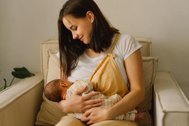 어머니의 가슴에서 우유를 빠는 신생아 아기. 엄마와 모유 수유 아기의 초상화. 건강하고 자연적인 아기 모유 수유 영양의 개념.