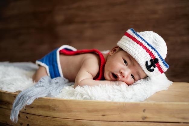 Новорожденный мальчик в бело-синей матросской шляпе