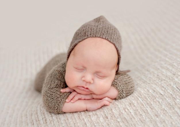니트 옷을 입고 신생아 아기는 뺨에 손을 넣어 잔다