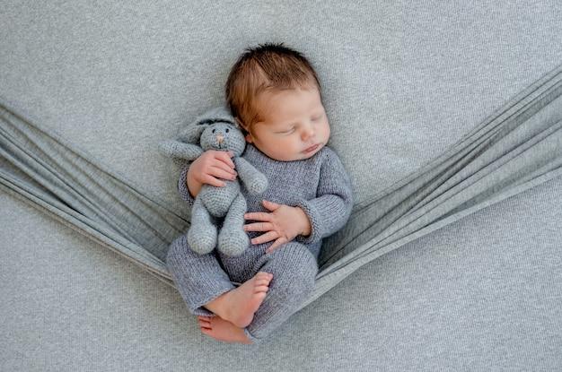 해먹에서 자고 손에 장난감을 들고 니트 의상을 입고 신생아. 장식이 있는 유아 어린이 스튜디오 초상화