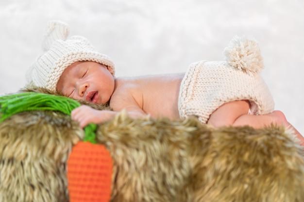 Newborn baby in bunny costume sleeping on fur bed