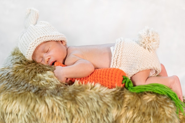 Newborn baby in bunny costume sleeping on fur bed