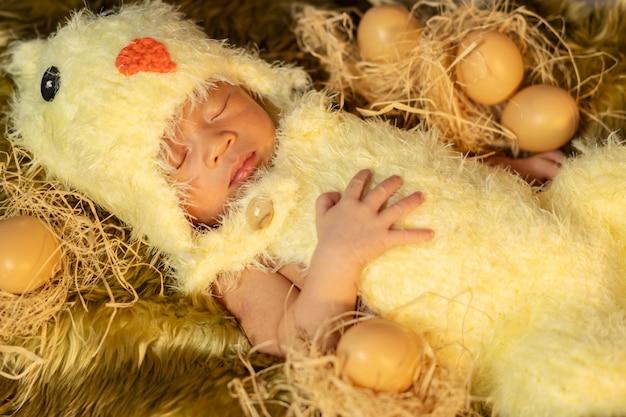 Newborn baby in chicken costume sleeping on fur bed