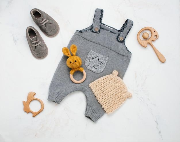 Одежда для новорожденных и мешочек на мраморе