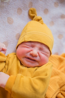 Newborn baby cries from gas, colic. a child born in the fall. newborn in the hospital  a child born in the fall. newborn in the hospital