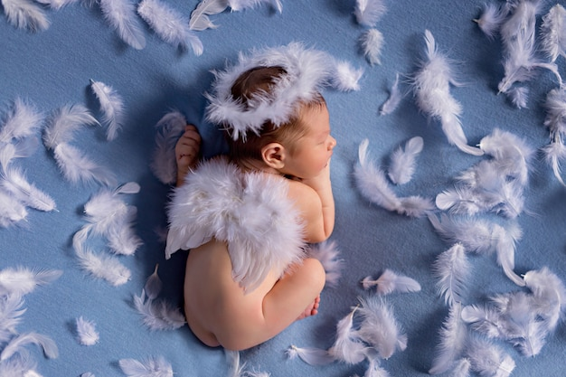 Newborn baby in a cupid costume with angel wings