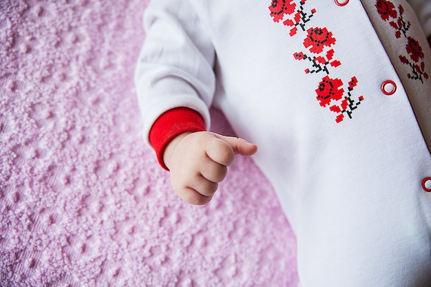 Newborn baby dressed in costume with embroidery