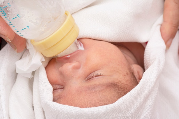 Newborn baby eating milk from small plastic milk bottle