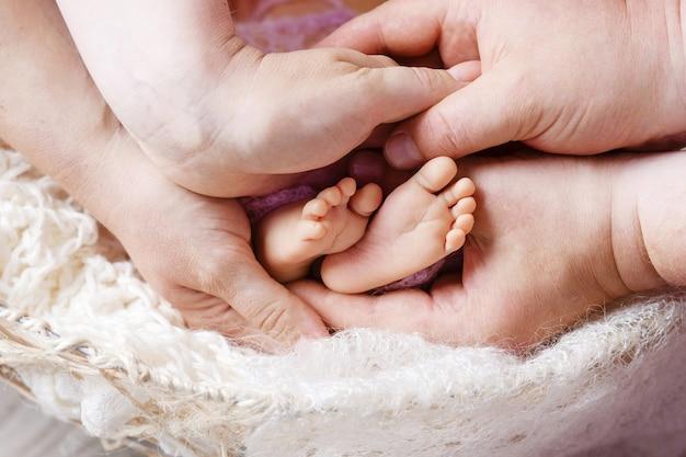 母と父の手で生まれたばかりの赤ちゃんの足。子供の足を手に持っている親。画像をクローズアップ。親子関係の美しい概念的なイメージ