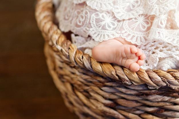透かし格子縞の生まれたばかりの赤ちゃんの足。クローズアップ写真。小さな生まれたばかりの赤ちゃんの足のクローズアップ。