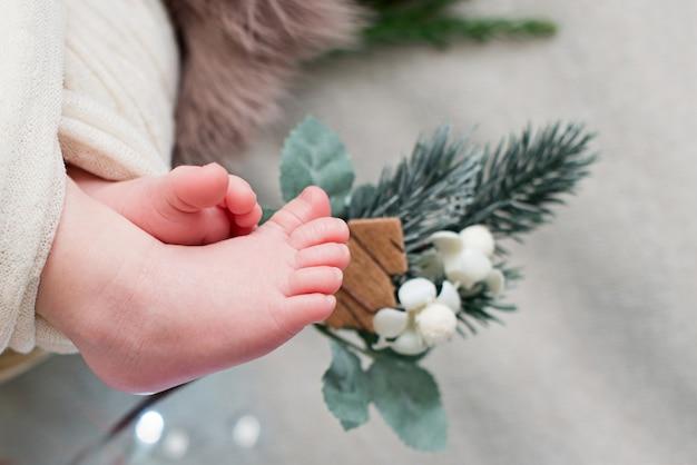 Ножки новорожденного с рождественскими украшениями.