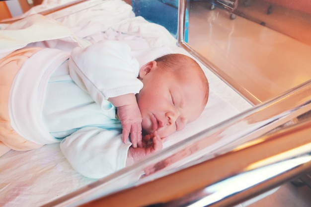 Newborn baby first days of life in delivery room. infant asleep in hospital after childbirth.