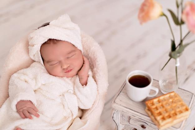 生まれたばかりの赤ちゃんの女の子。スパでのトリートメントの後、新生児はバスローブの椅子に横たわっています。